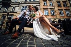 A noiva e o noivo sentam-se no banco Fotos de Stock Royalty Free
