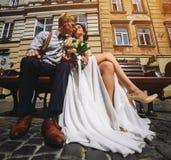 A noiva e o noivo sentam-se no banco Imagem de Stock Royalty Free
