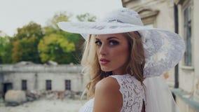 Noiva elegante em uma mão tocante do chapéu branco grande video estoque