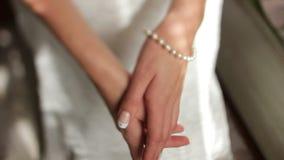 A noiva em pancadinhas de um vestido de casamento do branco ele mesmo no braço vídeos de arquivo