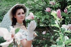 Noiva em um chapéu perto de uma flor cor-de-rosa imagens de stock royalty free