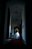 A noiva em um grande corredor escuro está na janela em seu w imagem de stock