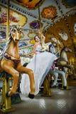 Noiva em um passeio do carrossel do recinto de diversão Fotos de Stock