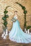 Noiva em um vestido bonito de turquesa em antecipação ao casamento Louro no verde de mar do vestido do laço com um ramalhete Noiv Fotografia de Stock