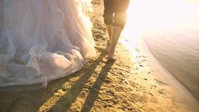 Noiva em um vestido branco e o noivo que anda com os pés descalços na água no banco de rio Close-up Movimento lento amar video estoque