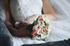 Noiva em um vestido branco que guarda um ramalhete imagens de stock royalty free