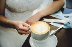 A noiva em um vestido de casamento bebe o café em um café fotografia de stock