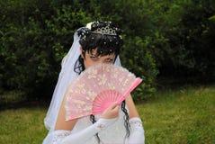 A noiva em um vestido de casamento está sentando-se no parque, cobrindo ele fotografia de stock