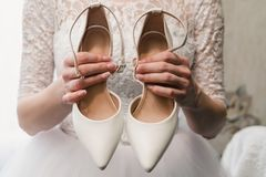 A noiva em um vestido de casamento guarda as sapatas brancas nas mãos bem arrumados com um tratamento de mãos bonito foto de stock royalty free