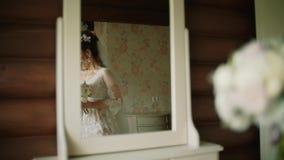 A noiva em um vestido de pingamento de seda branco anda avante no espelho video estoque
