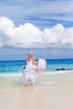 A noiva em wedding um vestido funciona na costa do oceano imagens de stock