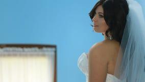 A noiva encantador lindo em um vestido luxuoso olha playfully sobre seu ombro Moça sensual bonita em um branco filme