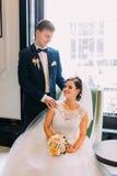 A noiva encantador senta-se na cadeira que guarda o ramalhete do casamento e o noivo afiado-vestido está próximo Janela de brilho imagens de stock royalty free