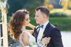 Noiva encaracolado elegante e noivo feliz fora no fundo o lago fotografia de stock royalty free