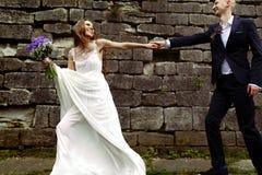 A noiva envolve um noivo que anda ao longo de uma parede de pedra grande Foto de Stock Royalty Free