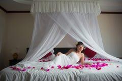A noiva está encontrando-se em uma cama branca nas pétalas cor-de-rosa no hotel imagens de stock royalty free
