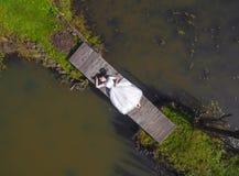 A noiva está encontrando-se em uma ponte de madeira, com os pés descalços Vista superior Fotografia de Stock Royalty Free