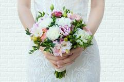 A noiva está guardando um ramalhete das flores em suas mãos fotos de stock royalty free