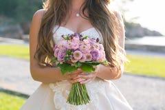 A noiva está guardando um rosa e um ramalhete lilás do casamento de várias flores fotos de stock