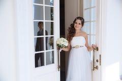 A noiva está na porta do salão do casamento, sorri e chama seu homem para ir com ela A silhueta do indivíduo é fotos de stock