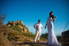 A noiva está no primeiro plano e o noivo está no fundo nas montanhas sob o céu azul no por do sol Fotos de Stock Royalty Free