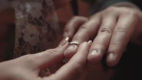A noiva est? pondo um anel de noivado sobre o dedo do noivo durante a cerim?nia de casamento, close-up, movimento lento video estoque