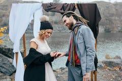 A noiva está pondo uma aliança de casamento sobre um momento do dedo do ` s do noivo, o feliz e o alegre Cerimônia de casamento d Foto de Stock Royalty Free