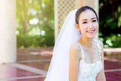A noiva está sentando-se com flores Jovem mulher bonita que levanta no parque Imagem de Stock Royalty Free