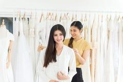 Noiva fêmea asiática que tenta no vestido de casamento, desenhista da mulher que faz o ajuste com a fita de medição no estúdio da fotografia de stock royalty free
