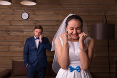 Noiva feliz contra o noivo que fala no telefone imagem de stock