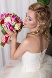 Noiva feliz da moça delicada bonita em um vestido branco que senta-se em uma cadeira e que cheira um ramalhete nupcial com um tra Foto de Stock Royalty Free