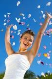 Noiva feliz e pétalas coloridas no céu azul Fotos de Stock Royalty Free