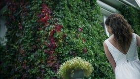 A noiva feliz em um vestido branco está dançando no jardim video estoque