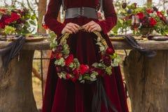 A noiva gótico da menina que veste um vestido vermelho de brocado guarda uma grinalda de imagens de stock