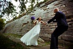 A noiva gerencie a um noivo ao longo de um trajeto atrás de uma parede de pedra velha Imagem de Stock