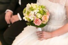 A noiva guarda o bouqet agradável do casamento que senta-se atrás de um noivo Foto de Stock Royalty Free