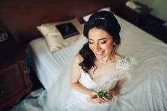 A noiva guarda pouco boutonniere branco em seus braços fotografia de stock