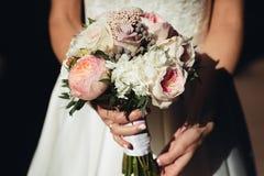 A noiva guarda um ramalhete do casamento das peônias em suas mãos fotografia de stock