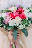 A noiva guarda um ramalhete do casamento de flores diferentes em suas mãos Fim acima foto de stock