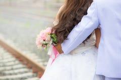 A noiva guarda um ramalhete do casamento, vestido de casamento, aliança de casamento, detalhes do casamento fotos de stock