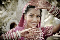 Noiva hindu indiana bonita nova que está sob a árvore com as mãos pintadas levantadas Fotografia de Stock
