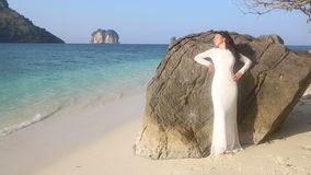 a noiva inclina-se na rocha na praia contra ilhas tropicais filme