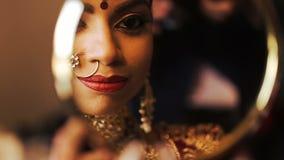A noiva indiana olha sua reflexão no espelho