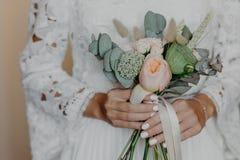 A noiva irreconhecível com tratamento de mãos macio, ramalhete bonito das posses, veste o vestido de casamento branco Ocasião esp Fotografia de Stock Royalty Free