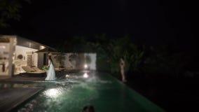 A noiva joga um ramalhete no casamento Festa na piscina na noite vídeos de arquivo