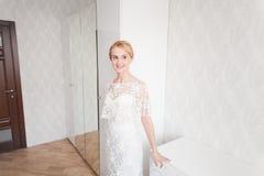 Noiva lindo com composição do ramalhete do casamento e penteado no vestido nupcial em casa que espera o noivo Imagens de Stock