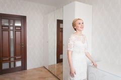 Noiva lindo com composição do ramalhete do casamento e penteado no vestido nupcial em casa que espera o noivo Foto de Stock Royalty Free