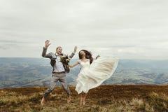 Noiva lindo feliz e noivo à moda que saltam e que têm o divertimento, b Fotografia de Stock