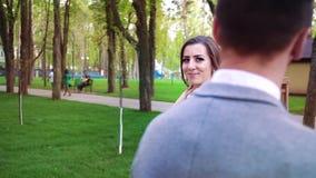 Noiva lindo que sorri e que anda em torno do noivo que est? ainda no parque ensolarado vídeos de arquivo