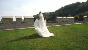 A noiva loura à moda feliz no vestido longo bonito tunning ao longo do jardim de florescência filme